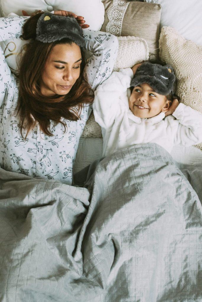 Mutter und Kind schlafen im gemeinsamen Bett unter einer Therapiedecke.