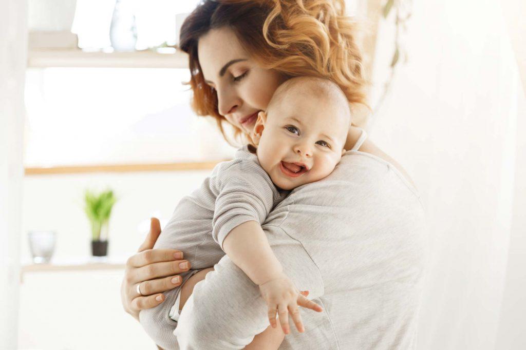 Mutter hält ihr Baby und schüttet dabei Oxytocin aus.
